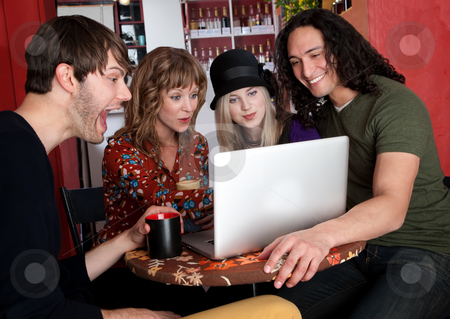 Funny Video stock photo, Four friends enjoying a video on a laptop at a cafe by Scott Griessel