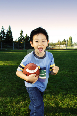 Football boy stock photo, A happy boy playing football outdoor by Suprijono Suharjoto