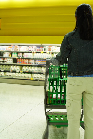 Grocery shopping stock photo, A woman shopping for milk at a grocery store/supermarket by Suprijono Suharjoto