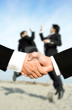 Success businessmen shaking hands stock photo, Two businessmen shaking hands with other two businessmen celebrating in the background, can be used for success concept by Suprijono Suharjoto