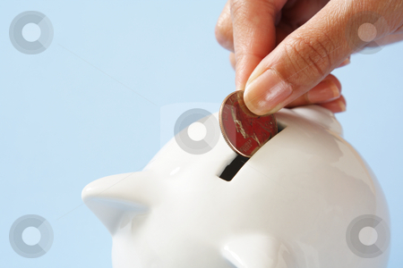 Money saving stock photo, A woman saving a coin into a piggy bank by Suprijono Suharjoto