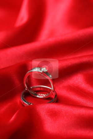 Wedding rings stock photo, A pair of wedding rings on a red fabric by Suprijono Suharjoto