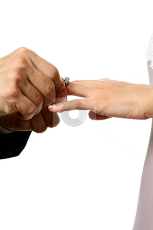 Wedding stock photo, The groom inserting a diamond wedding ring into the bride's finger by Suprijono Suharjoto