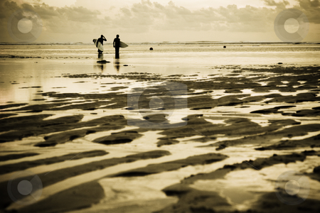 Surfers at the beach stock photo, Two surfers at the beach during sunset by Suprijono Suharjoto