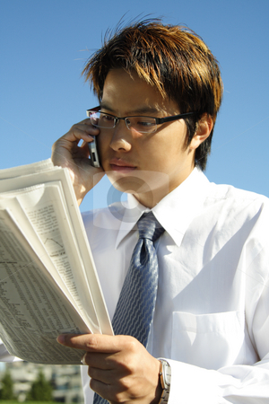Reading businessman stock photo, Businessman reading a financial newspaper while making a phone call by Suprijono Suharjoto