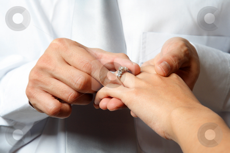 Wedding  stock photo, The groom inserting a diamond ring into the bride's finger by Suprijono Suharjoto