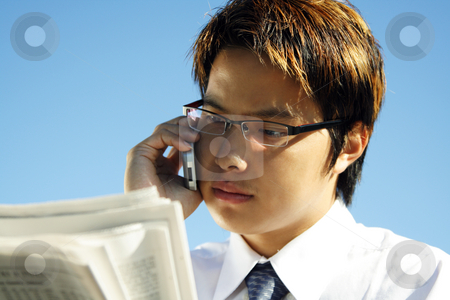 Busy businessman stock photo, Businessman reading financial newspaper while making a phone call by Suprijono Suharjoto
