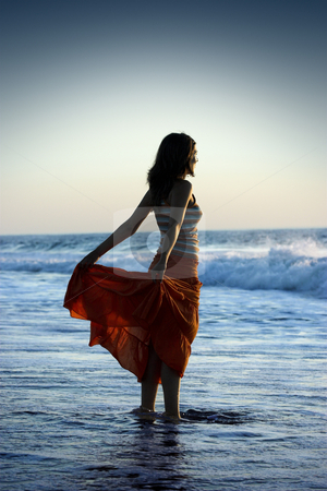 Beach Woman stock photo, Woman silhouette on the beach holding her skirt by ikostudio