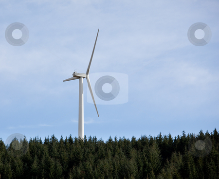 Single wind electricity generator stock photo, Large wind based electricity turbine rising above the tree line against a blue sky by Steven Heap