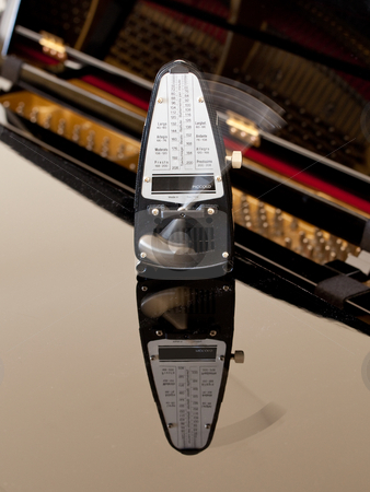 Metronome ticking and reflected on piano stock photo, Metronome and reflection caught in motion on the black lacquered lid of a piano with the interior strings visible by Steven Heap