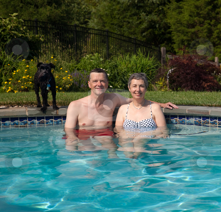 Couple in pool in yard stock photo, Senior couple relax in pool with pet dog on the edge of the pool by Steven Heap