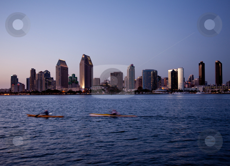 San Diego skyline on clear evening with kayaks stock photo, Sun setting lights up the buildings on San Diego seafront with kayaks and canoes by Steven Heap