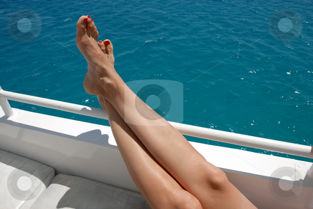Woman legs on yacht stock photo, Woman crossed legs on yacht over blue sea by Julija Sapic