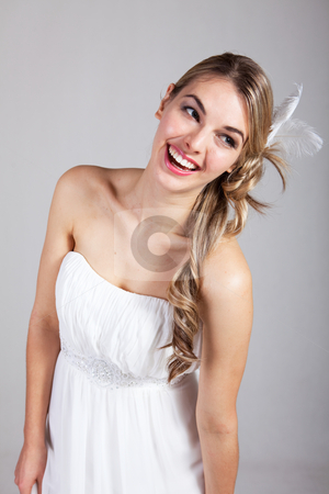 Attractive Young Woman in a White Dress stock photo, Attractive young woman wearing a white strapless dress and a feather hairpiece poses and laughs. Vertical shot. by Angela Hawkey