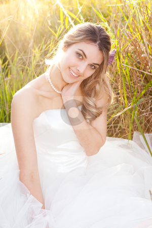 An attractive young bride wearing a white wedding dress and pearls is