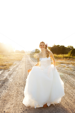 An attractive young bride wearing a white wedding dress is standing in the
