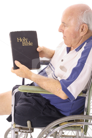Elderly man in wheelchair reading the bible stock photo, Elderly man in wheelchair reading the bible by Andi Berger