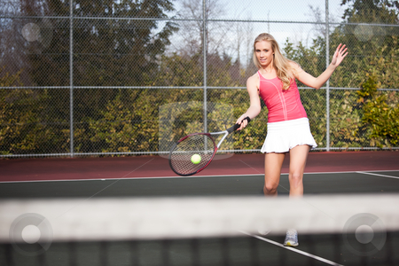 Tennis player stock photo, A beautiful caucasian tennis player hitting the ball on the tennis court by Suprijono Suharjoto