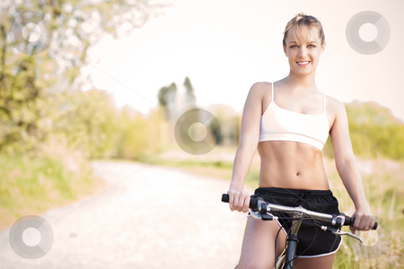 Sport woman stock photo, A sporty woman riding a bicycle outdoor by Suprijono Suharjoto