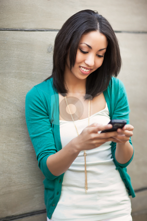 Black woman texting stock photo, A beautiful black woman texting on her phone by Suprijono Suharjoto