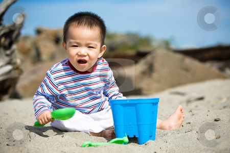 Beach boy stock photo, A cute asian boy playing with sand on the beach by Suprijono Suharjoto