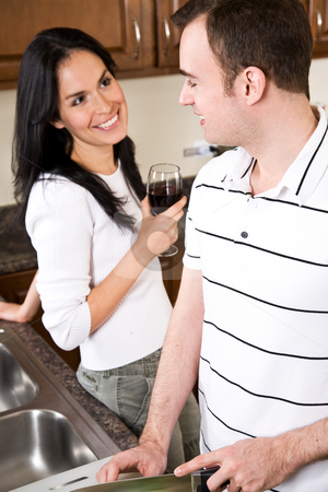 Young couple in the kitchen stock photo, A beautiful interracial couple preparing food and having a conversation in the kitchen by Suprijono Suharjoto