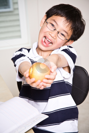 Studying kid holding an apple stock photo, A shot of an asian kid studying and holding an apple at home by Suprijono Suharjoto