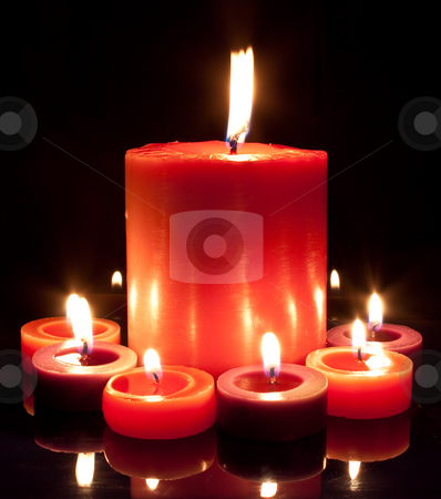 Red Candles - Large and small stock photo, A large red candle surrounded by small red and purple by Stephen Clarke