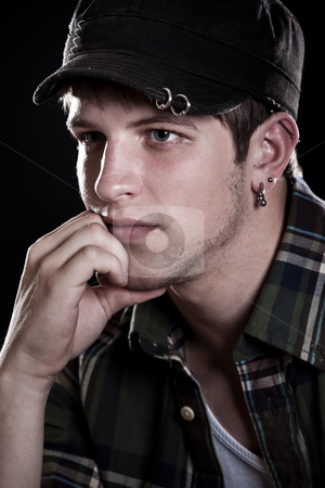 Pondering Caucasian young man wearing hat stock photo, Stressed young man by Suprijono Suharjoto