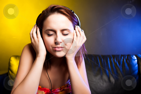 Beautiful woman with headphones stock photo, A shot of a beautiful caucasian woman sitting on the sofa listening music with headphones by Suprijono Suharjoto