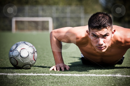 Hispanic soccer or football player stock photo, A shot of a hispanic soccer or football player doing a push-up by Suprijono Suharjoto