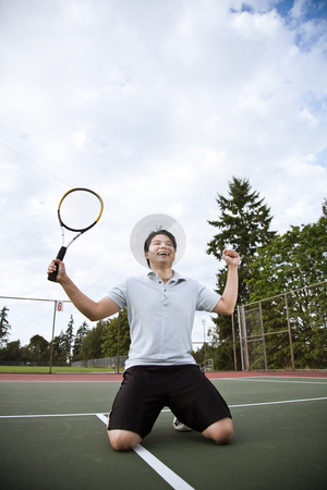 Asian tennis player in joy after winning stock photo, A happy asian male tennis player in joy after winning by Suprijono Suharjoto