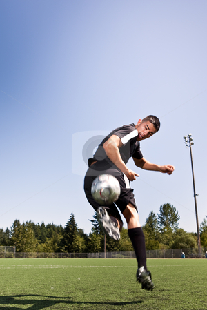 Hispanic soccer or football player kicking a ball stock photo, A shot of a hispanic soccer or football player kicking a ball by Suprijono Suharjoto