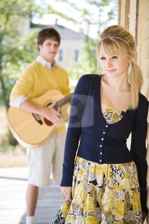 Young caucasian couple in love stock photo, A young caucasian man in love singing to his beautiful girlfriend by Suprijono Suharjoto