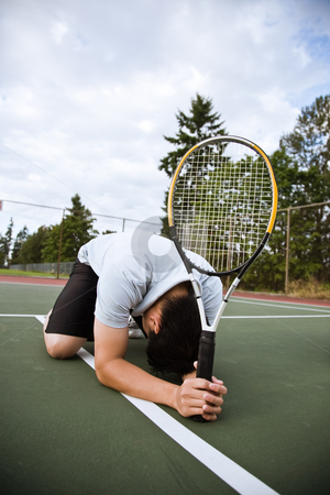 Sad tennis player after defeat stock photo, A sad asian tennis player kneeling down in disappointment after defeat by Suprijono Suharjoto