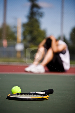 Sad tennis player after defeat stock photo, A sad male tennis player sitting down in disappointment after defeat by Suprijono Suharjoto