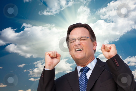 Excited Businessman  Expresses His Excitement Outside stock photo, Excited Businessman in Suit and Tie Clinches His Fists in Joy with Dramatic Sun Rays, Clouds and Sky. by Andy Dean