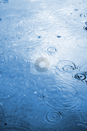 Raindrop Water Ripples stock photo, Illustration of raindrops hitting some blue water creating circular ripples. by Todd Arena