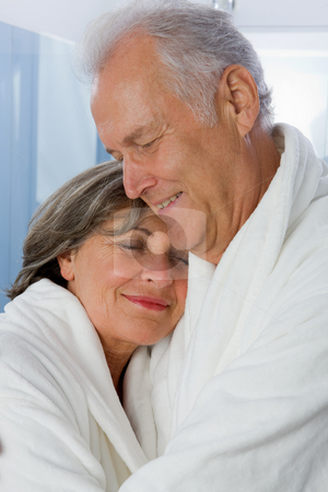 Senior Couple stock photo, Seniors in white Bathrobe hugging in Bathroom by Alexander Beck