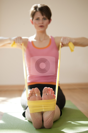 Young Woman Exercising With Resistance Bands stock photo, Attractive young woman exercises with resistance bands around her feet. Vertical shot. by Edward Bock