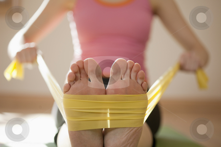 Woman Exercising With Resistance Bands stock photo, Woman exercises with resistance bands around her feet. Horizontal shot. by Edward Bock