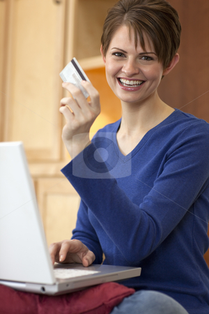 Young Woman Shopping Online stock photo, Attractive young woman holds up the credit card she is using to shop with on her laptop computer. Vertical shot. by Edward Bock