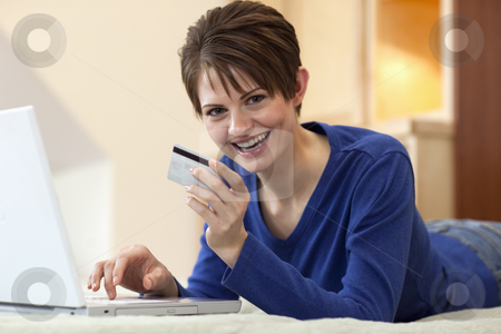 Young Woman Shopping Online stock photo, Attractive young woman holds up the credit card she is using to shop with on her laptop computer. Horizontal shot. by Edward Bock
