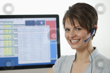 Attractive Young Businesswoman With a Headset stock photo, An attractive young businesswoman is wearing a headset and smiling at the camera with a computer monitor in the background. Horizontal shot. by Edward Bock