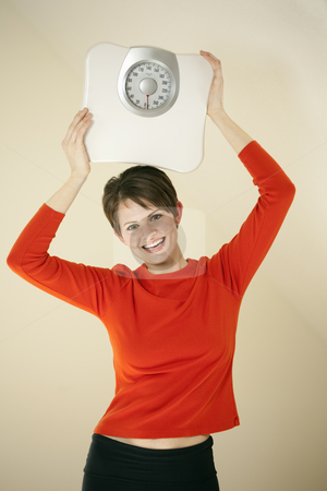 Attractive Woman Holding a Bathroom Scale stock photo, Attractive young woman holds a bathroom scale above her head while smiling at the camera. Vertical shot. by Edward Bock