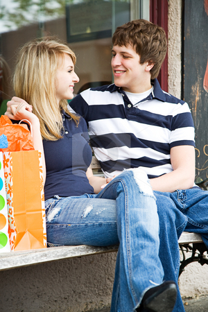 Shopping young caucasian couple stock photo, A young caucasian couple sitting and talking on a bench after shopping by Suprijono Suharjoto