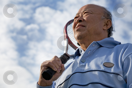 Senior tennis player stock photo, A shot of a senior asian man holding a tennis racquet by Suprijono Suharjoto
