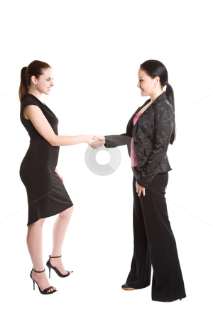 Two businesswomen shaking hands stock photo, An isolated shot of two businesswomen shaking hands by Suprijono Suharjoto