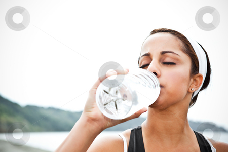 Sporty woman drinking water stock photo, A beautiful asian woman drinking water after exercise by Suprijono Suharjoto