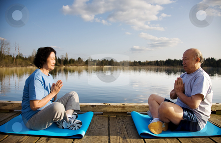 Senior exercise stock photo, A shot of a senior couple practicing a yoga exercise and meditating outdoor by Suprijono Suharjoto